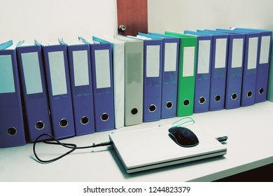 Folders with notebook on table in office