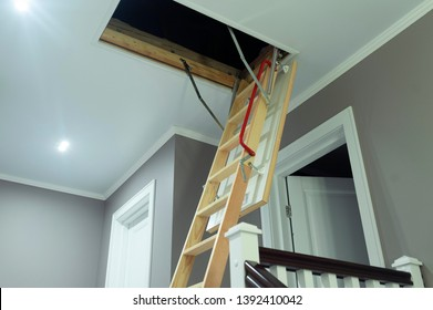 folding attic ladder. Wooden pull down attic folding stairs in small hallway, space saving in home concept