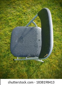 Folding chair, viewed from above is sitting on green grass. The chair is grey with water droplets collected on the vinyl seat material. Concept. Selective focus. Abstract.