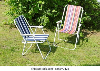 folding chairs on the lawn in the spring afternoon