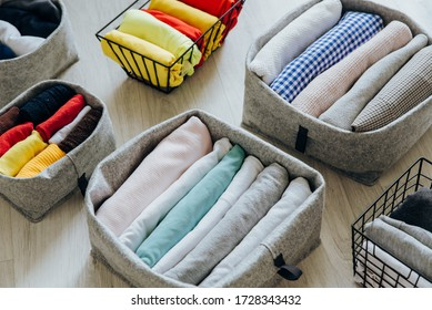 Folding clothes, organizing stuff in boxes and baskets. Concept of tidiness, minimalism lifestyle and japanese t-shirt folding system. Minimalist storage and arrangement in wardrobe