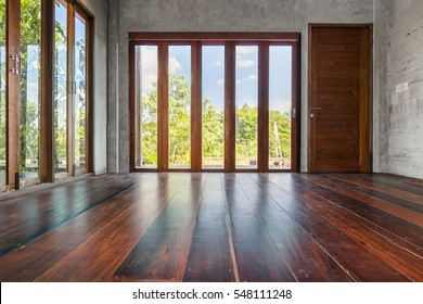 Folding doors with tall windows old wooden floor in empty living room interior