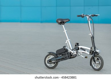 Folding electric bike outdoors on blue and grey background