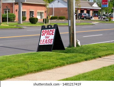 A folding A Frame plastic sign by the curb advertising Space For Lease.