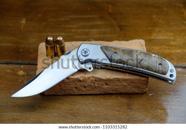 A folding knife is placed on a red brick and the bearing on a wooden floor.