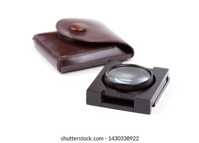 Folding loupe, numismatic coin magnifier with a brown leather case foldable linen tester magnifier, thread counter, tool for line measurement and inspection isolated on white