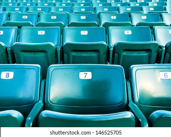 Folding numbered stadium seats in a green color.   Seats are in an outdoor stadium.