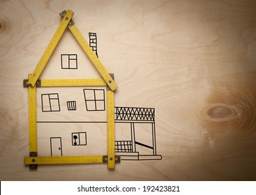 Folding rule setting up in shape of a house on wooden background. House consept.