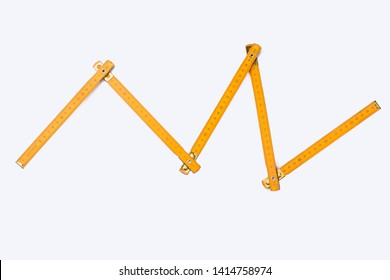 Folding ruler on white background. Image of yellow wooden yardstick. Carpenters tool with scale of numbers.