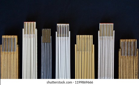 Folding rulers are lined up in a row to suggest varying heights or measurements, even a skyline, with both metric and English scales represented