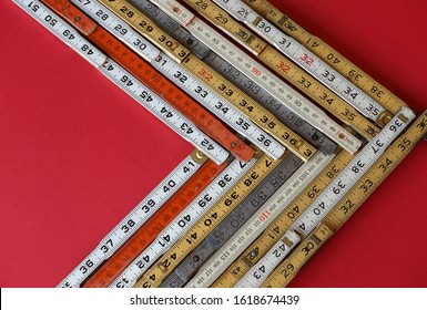 Folding rulers in metric and inches on red background form a chevron chart or graph representing accuracy, measurement, increase, growth and results with copy space.