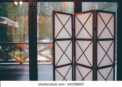 Folding screen beside the window at rainy weather with the backyard view