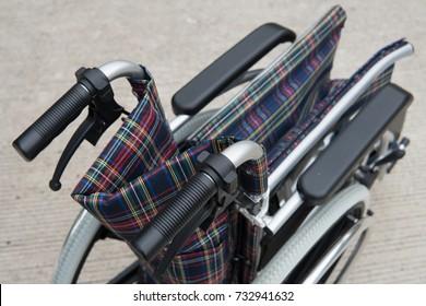 folding wheelchair selective focus on handgrip.