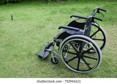 folding wheelchair standing on grass