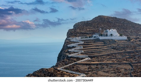 Folegandros island, Greece, Cyclades. Panagia Virgin Mary Church and long zigzag road aerial drone view. Traditional cycladic whitewashed church on top of a steep hill overlooking Chora and Aegean Sea