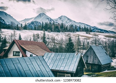 Folk architecture in Zdiar village with Belianske Tatry mountains, Slovak republic. Winter holiday resort. Travel destination. Analog photo filter with scratches.