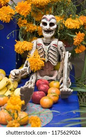 Folk art skeleton, flowers and fruit on traditional altar for Day of the Dead festival, Oaxaca, Mexico