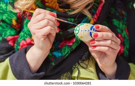 Folk female artist painting traditional easter egg