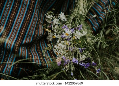 Folk girl making wreath of flowers for the midsummer event