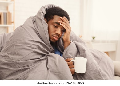 Folk medicine. Sick african american guy with fever wrapped in warm blanket drinking hot tea, free space
