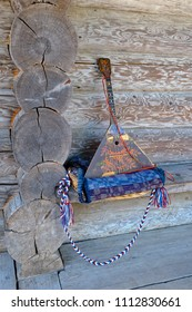 Folk musical instrument balalaika on wooden bench in front of old log peasant house wall.