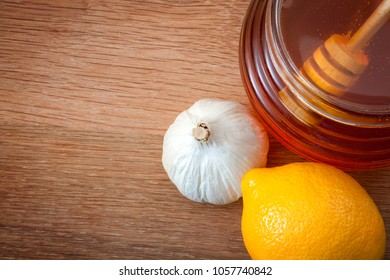 Folk natural remedy for flu and cold, strengthen immunity during winter and alternative medicine concept with close up on a jar of honey with a honey dipper, fresh garlic and lemons with copy space