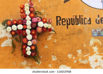 Folk style wreath on weathered orange wall in Guatemala City