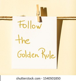 Follow the Golden rule note hanging by a clothespin and twine on yellow background
