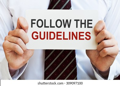 Follow the Guidelines. Man holding a card with a message text written on it