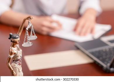 Follow the law. Professional lawyer sitting at the table and signing papers with justice statue standing on surface in forefront.