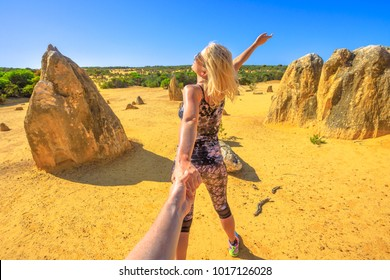Follow me, attractive sporty blonde girl holding hands at Pinnacles Desert in Nambung National Park, Cervantes, Western Australia. Concept of the journey of woman tourist traveler, holding man by hand