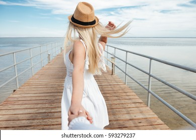 Follow me. Attractive young woman in hat holding hand of her friend and walking on pier