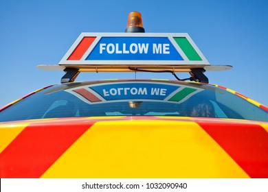 Follow me banner on airport service car.