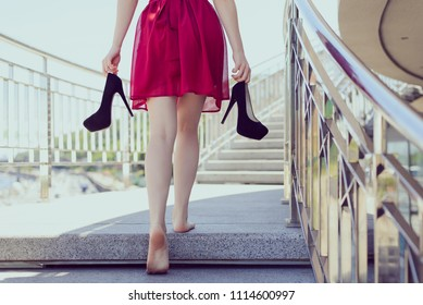 Follow me classic chic classy clothing after dancing prom concept. Gorgeous cute happy teen student holding black stilettos pumps in hands standing ground without shoes relaxing having rest chill out