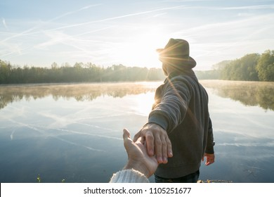 Follow me to concept, young man leading girlfriend to the lake at sunrise, people travel journey concept sharing. Personal perspective