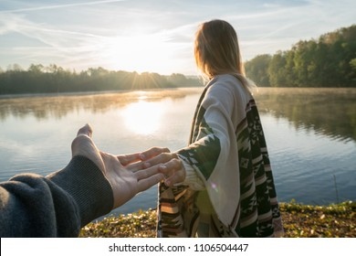 Follow me to concept, Young woman leading boyfriend to the lakeshore at sunrise, holding hands, People travel couple beginning. Shot in France, Europe