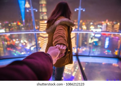 Follow me couple traveling in oriental pearl TV tower. Woman red hair in orange jacket holding man by hand going to night view of city in shanghai. Traveling together.