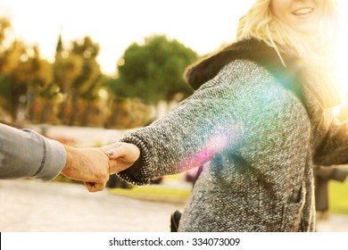 follow me - happy young hipster woman pulling guy's hand - hand in hand walking on a bright sunny day in autumn - concept of carefree modern life - focus on hands, sunburst and lens glare effects