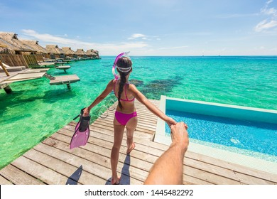 Follow me luxury travel vacation couple following woman snorkeling at overwater bungalow hotel. Man holding hand following woman in Bora Bora, Tahiti, French Polynesia. Watersport fun activity.