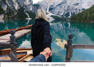 Follow me photo on beautiful landscape of Braies Lake (Lago di Braies), romantic place with wooden bridge and boats on the alpine lake, Alps Mountains, Dolomites, Italy, Europe