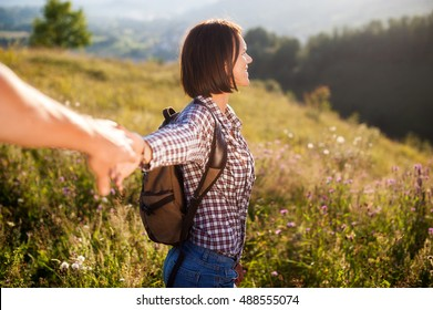follow me picture with focus on girl. traveler woman holding man's hand and leading him on nature outdoor