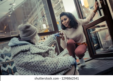 Follow me. Pleasant good looking woman giving her hand while inviting a poor aged woman inside