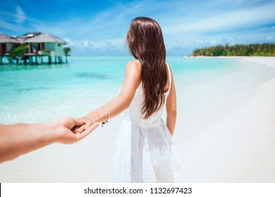 Follow me. Pretty young woman in white dress holding man's hand and leading her friend on a beach. Summer vacation photo.