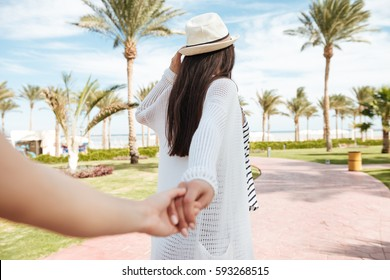 Follow me. Pretty young woman in hat holding hand and leading her friend on summer resort