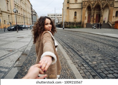 Follow me. Romantic concept. Young woman with long ginger hair outdoors holding boyfriend's hand.