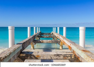 Follow me to the sea. Old boat dock perfectly leading to the majestic blue horizon. Clear, serene, turquoise waters at Grace Bay in Turks and Caicos Islands.