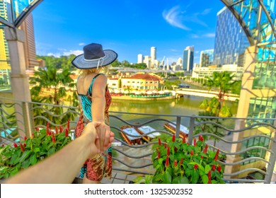 Follow me. Tourist woman with wide hat holding hand of partner looking panorama from terrace over Clarke Quay and Riverside area in Singapore, Southeast Asia. Lady enjoys on Singapore River downtown.
