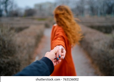 Follow me. Travel concept. Back view of young womanwith long ginger hair outdoors  holding boyfriend's hand.