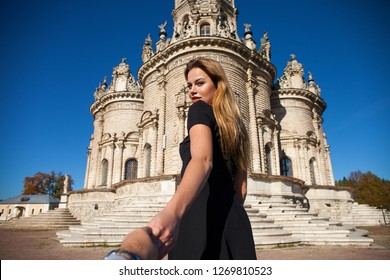 Follow me. Young beautiful woman in black dress on the background of the church