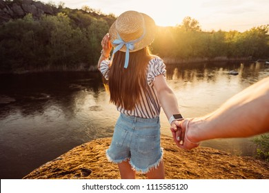 Follow me. Young woman in hat holding hand and leading man to the beautiful nature sunset landscape. View from back side, POV. Romantic couple travel, spend  summer vacation together outdoors.